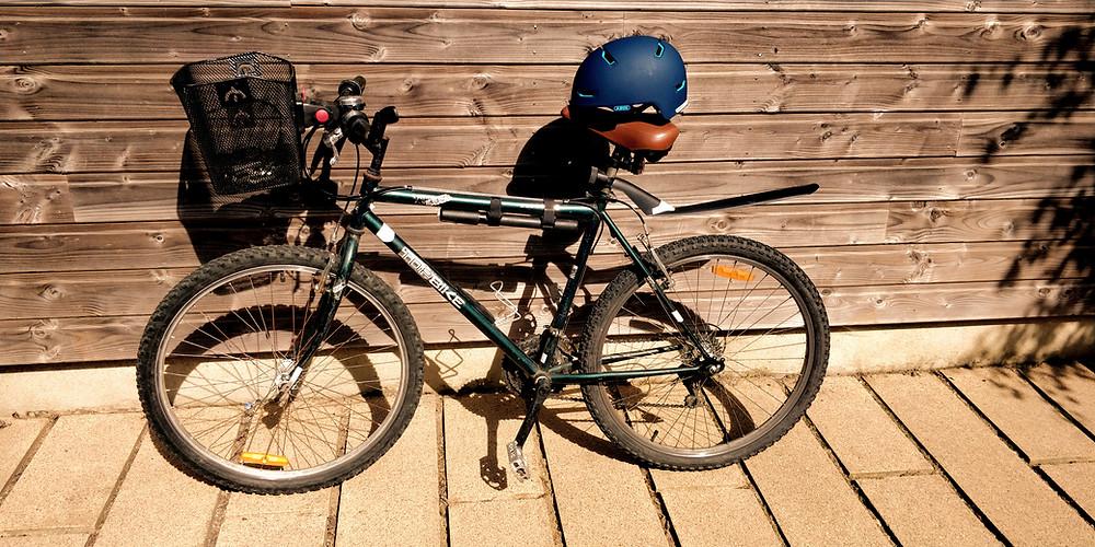 Photo d'un vélo VTC avec panier à l'avant et rétroviseur, casque posé sur la selle
