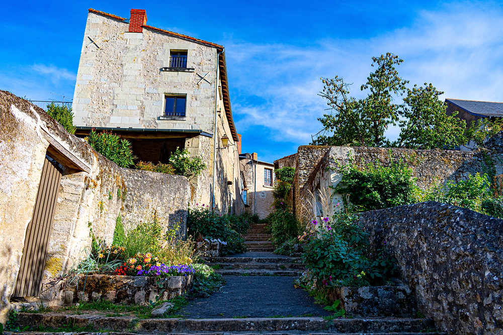 Escalier en pierre, entouré d'anciennes batisses et de vieux murs en pierre, le passage est fleuri