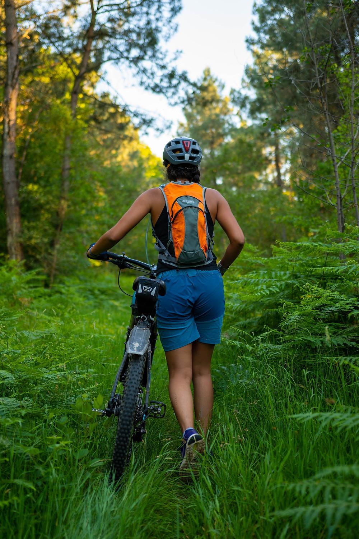 Une personne de dos avec un camelbag et un casque, qui pousse son vélo VTT dans les fougères de la forêt de Longuenée