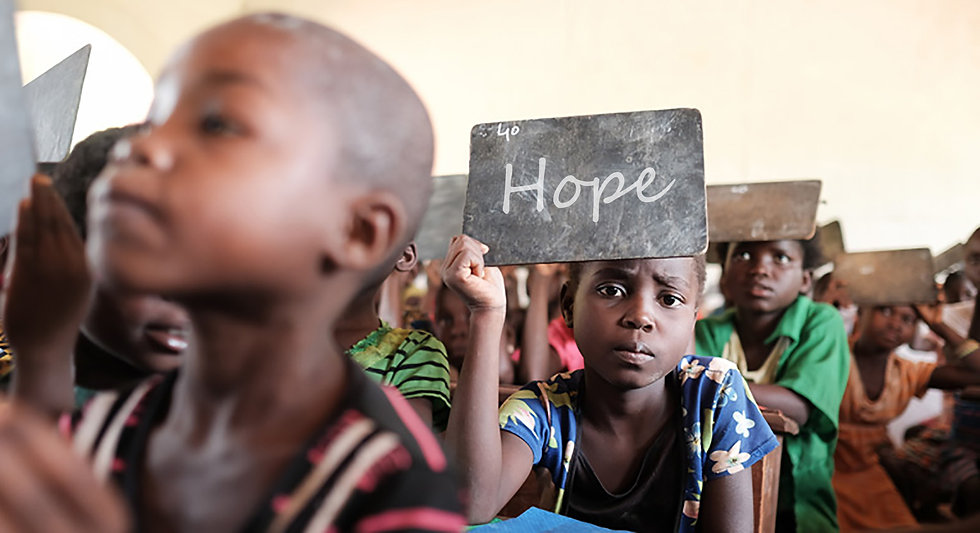 Cameroonian children in classroom holding up chalkboards with their names on