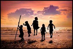 Children jumping on beach