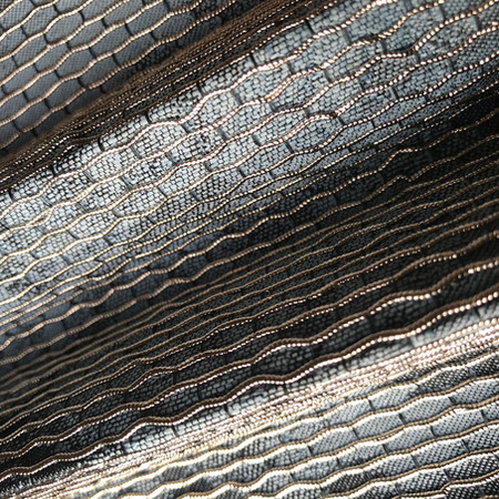 Woven fabric with integrated metal surface detail