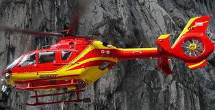 Red and yellow rescue helicopter in front of grey rock cliff