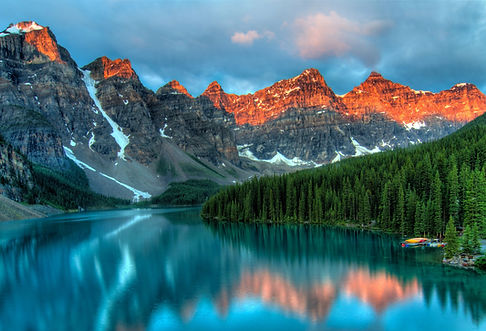 Snowy mountains with alpenglow behind a beautiful wilderness lake and forest hillside