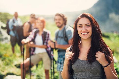 Smiling woman and hiking group on outdoor trail in the sun