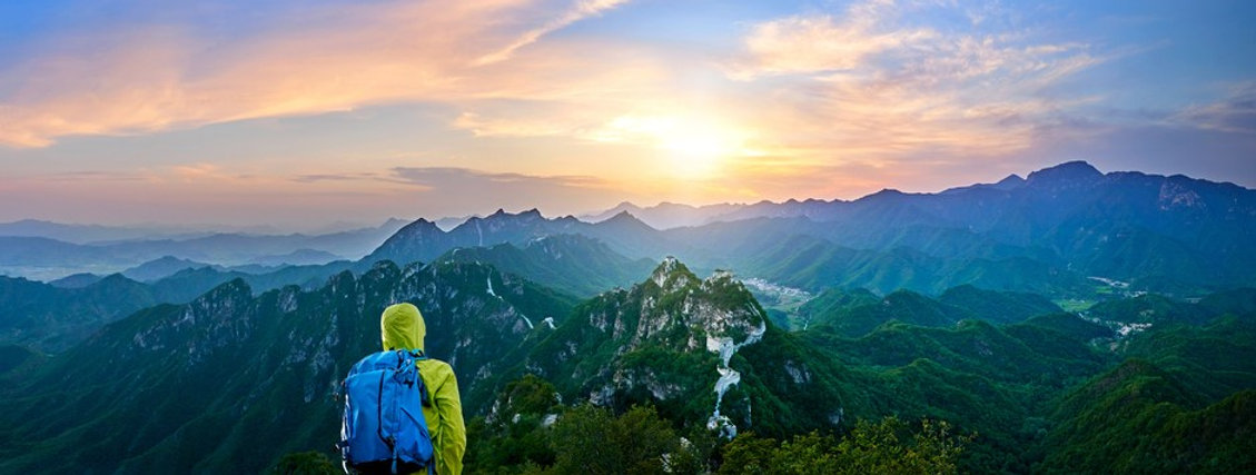 Backpacker on outdoor adventure environmental program looks out over sunset or sunrise vista of mountains