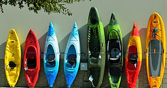 Colorful sit on top and decked kayaks for outdoor adventure program leaning against a wall