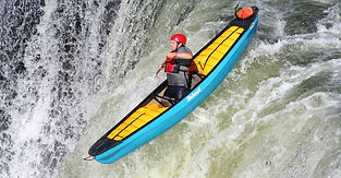 Whitewater paddler bracing as canoe goes down waterfall