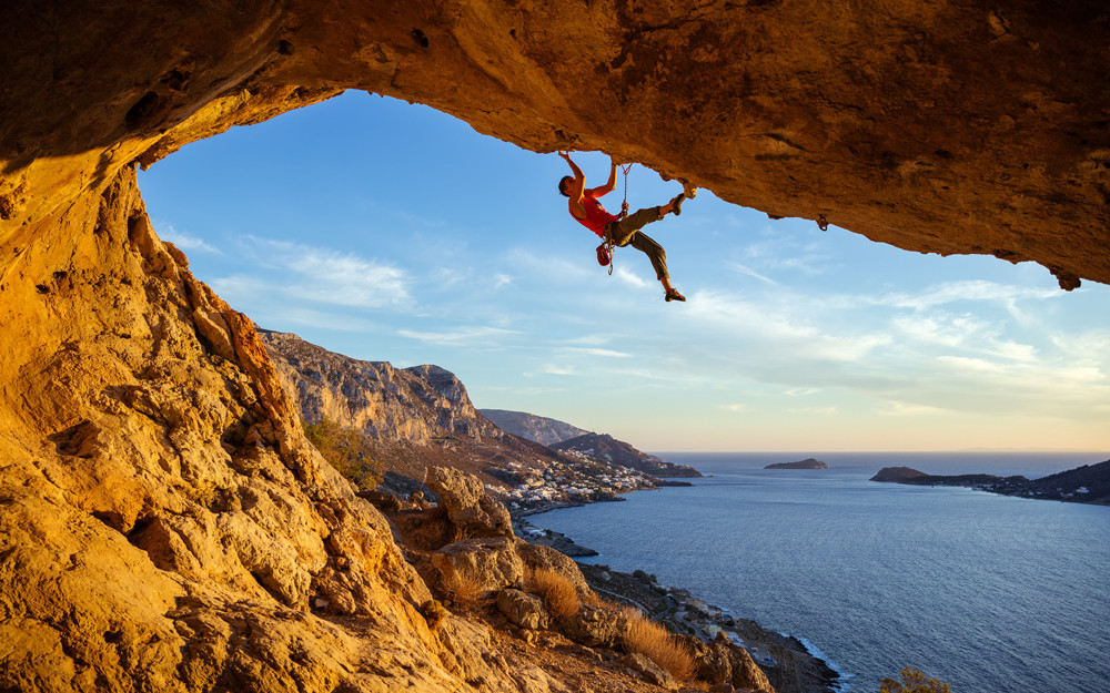 Rock climber on crag above the sea.  Rock climbing presents wilderness safety and outdoor risk management concerns, but real risks are low if climbing is managed well.