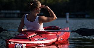 Woman outdoors in red kayak looking forward