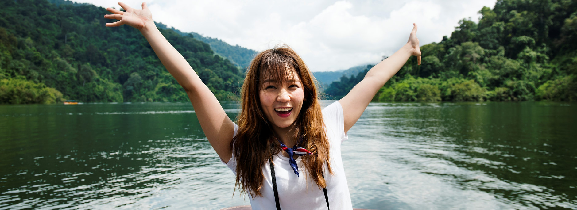 Satisfied outdoor adventure program customer smiling and holding her hands up in air in front of river and forested hills outdoors