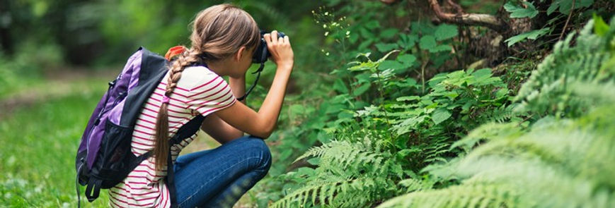 Girl looking through binoculars at an object outdoors during environmental education program