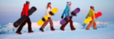 Snowboarders walking across snow holding their snowboards as part of a custom training in outdoor and experiential education