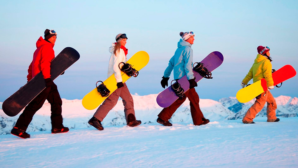 Snowboarders walking on snow carrying snowboards.  Outdoor safety and wilderness risk management are considerations for frontcountry and backcountry snow sports.