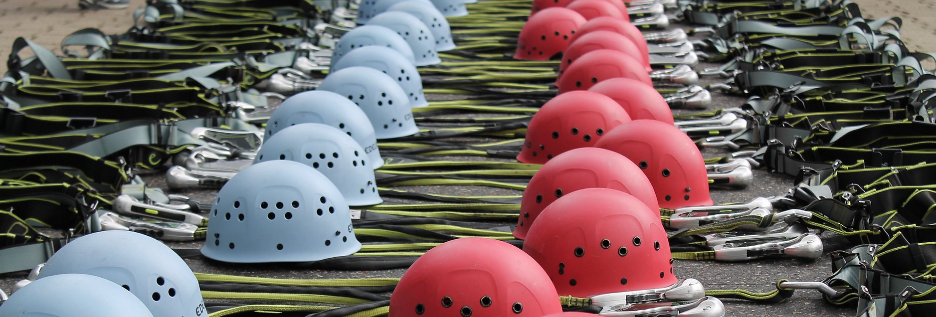Rock climbing helmets and technical gear displayed for an outdoor program risk management assessment