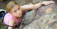 Girl on outdoor education program doing toprope rock climbing outdoors, looking upwards