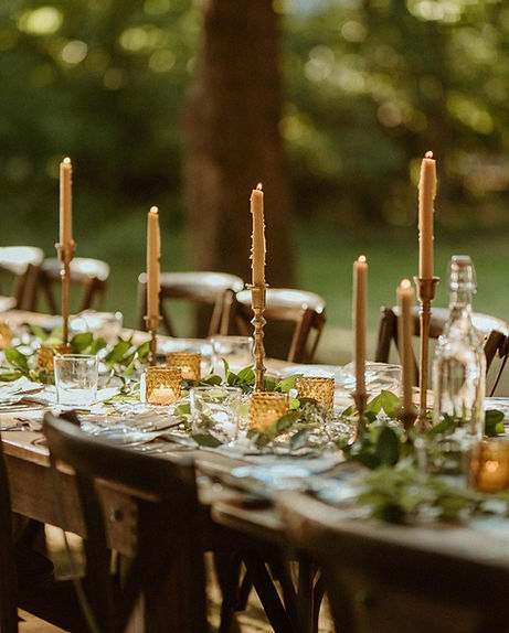 Farm table rental outside with candles and farm chairs for party