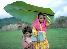 young children with school books walking in the rain