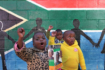 young children with fists screaming Amandla with Nelson Mandela Long Walk to Freedom book in front of South Africa flag