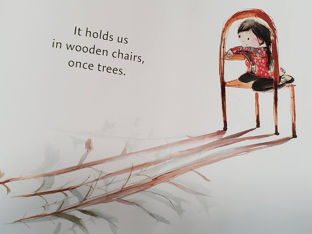 Image from book, Girl on wooden chair looking at the cast shadow that is of the trees that made the chair.