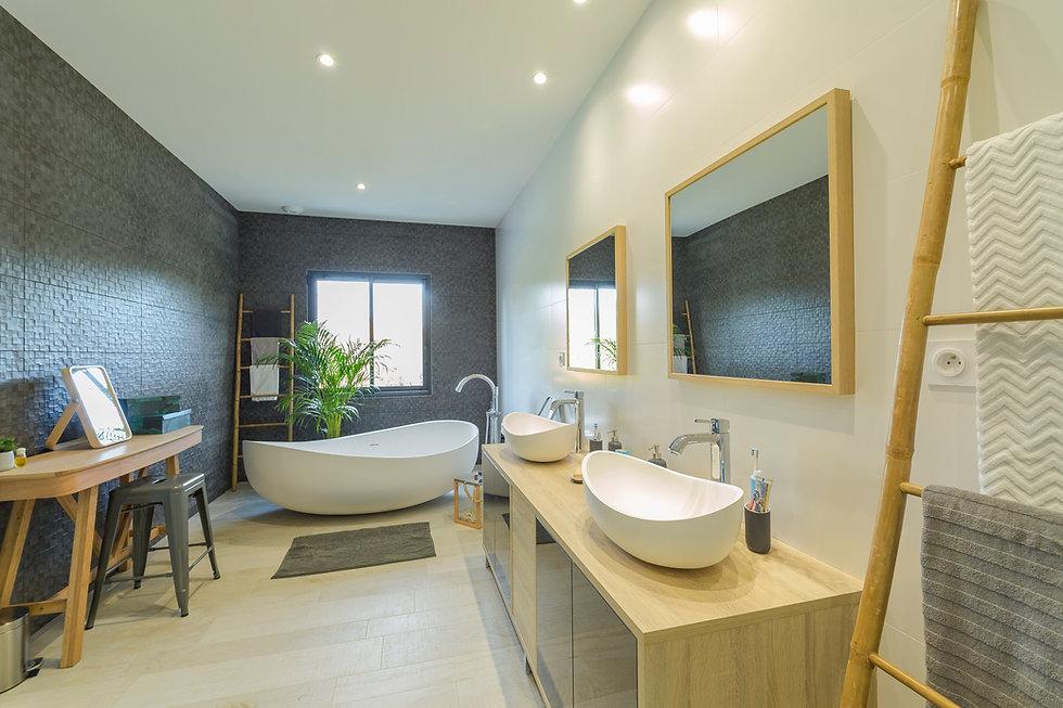 Salle de bains moderne avec baignoire îlot, double vasques. Matériaux dominants : blanc, gris anthracite, bois