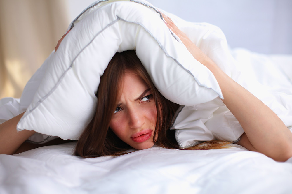 Female lying on bed and closing her ears with pillow..jpg
