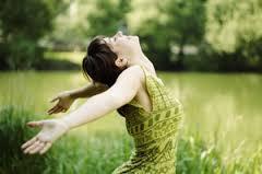 אישה פותחת ידיים ומביטה לשמיים בחיוך