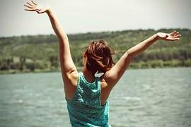 אישה מרימה ידיים לשמיים מול הים
