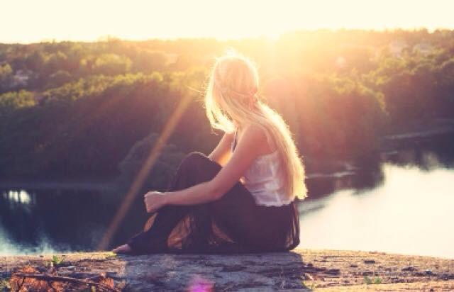 אישה יושבת על הנהר ומביטה לשקיעה