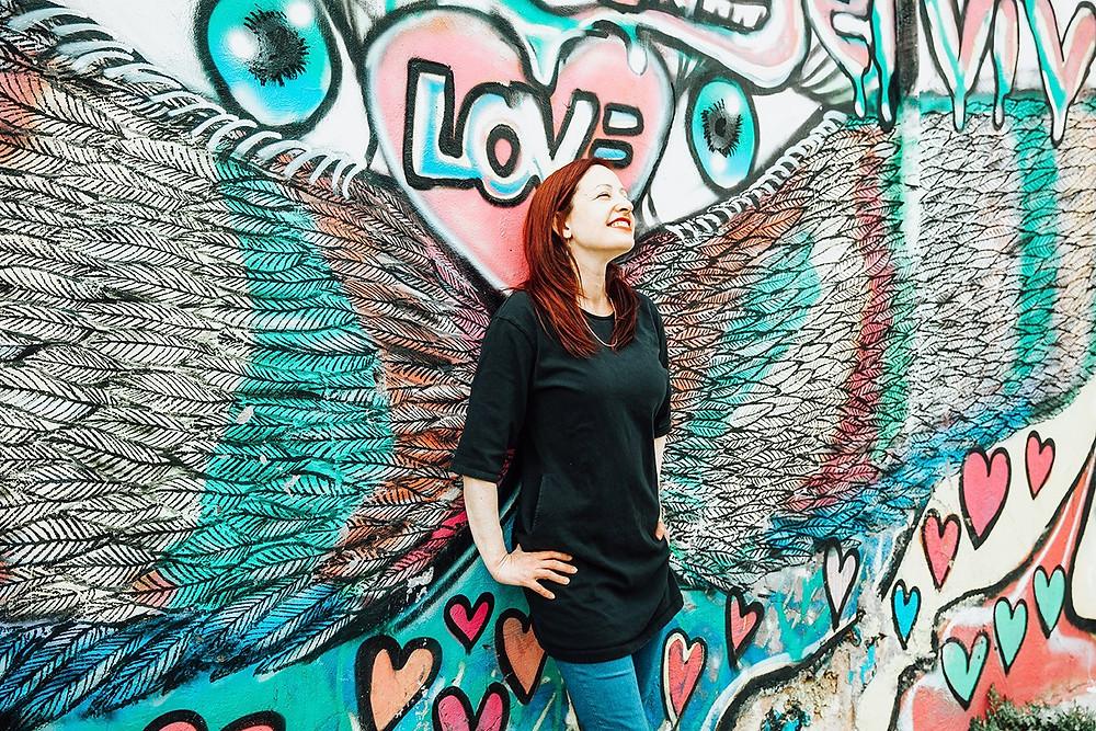 אביגיל נשענת על קיר מצויר עם כנפיים ומחייכת
