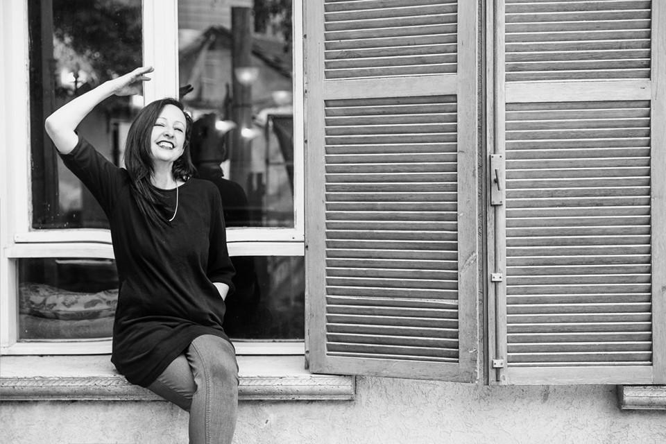 אישה יושבת על עדן החלון מחייכת