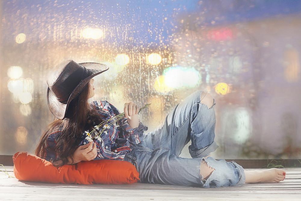 אישה שוכבת ומסתכלת על גשם מבעד לחלון
