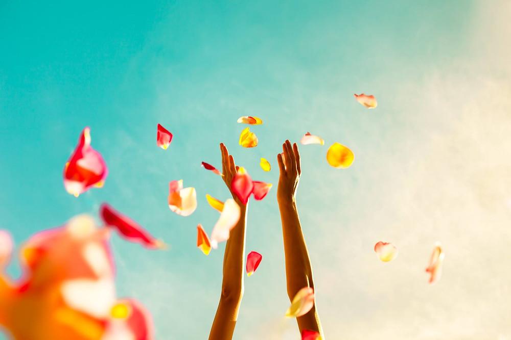 ידיים מושטות לשמיים ופרחים נופלים