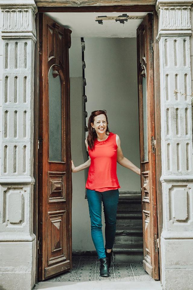 אביגיל עומדת בפתח של דלת ומחייכת