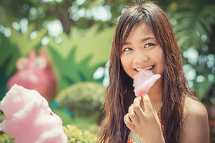 Cute Asian Thai girl is eating pink cand