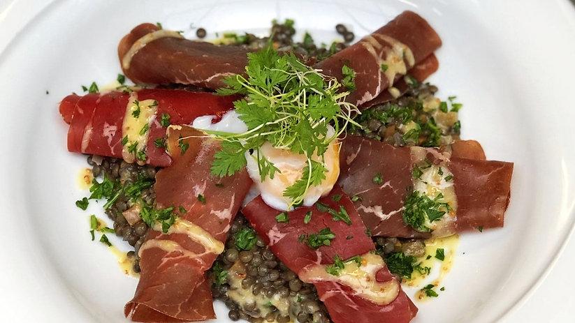 Salade de lentilles au jambon cru, servie avec un oeuf poché