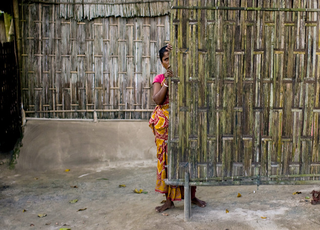 34.	A woman from the Rajbongshi tribe, one of the tribal communities in Assam's Goalpara district, peeks out from behind a wall in her village. Local says Bangladeshi are taking over the tribal land