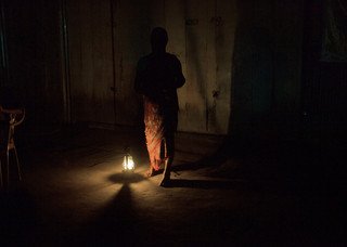 Women turn the kerosine lamp at her home in the Dhubri District of Assam. Some of the tribals are so poor that they had a hard time feeding their families