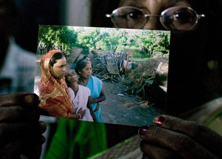 Portrait of Urmila Roy showing the photograph of herself and her mom, who fainted while some Bangladeshi gang members took over their property. Local police and local government are very corrupt in this border city.