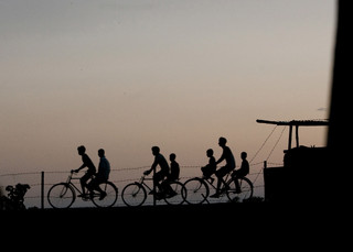 Bangladeshi cycling in the village of Satrasal at the Indian Border Patrol Check Post during the late evening before the curfew starts on the border region. Satrasal is located in the Dhubri District of Assam. These immigrant bribes $10 to $12 to cross the border, and once they come to India, they apply for false ration cards to vote. One hundred sixty miles long India-Bangladesh border area in Assam where some of the borders are fenced and the rest is open land. Poverty in Bangladesh is so dire that people are trying to cross illegally to India to find work. Most illegal immigrants travel to big cities like Mumbai to work as construction workers or other labor jobs to earn their leaving