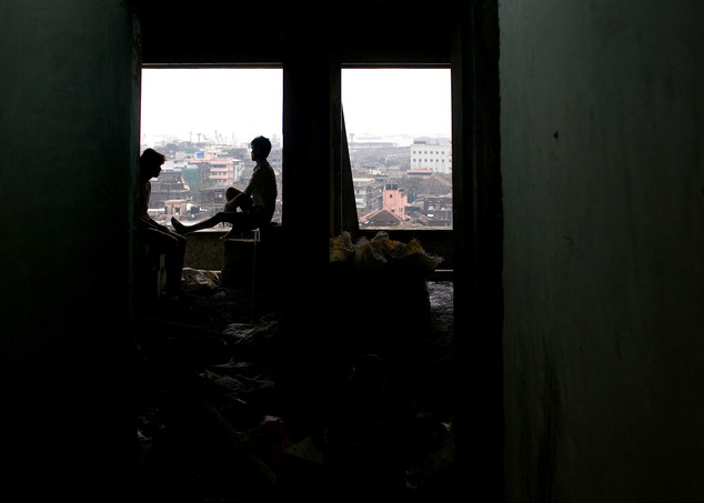 Bangladeshi workers rest while looking at the downtown Mumbai skyline