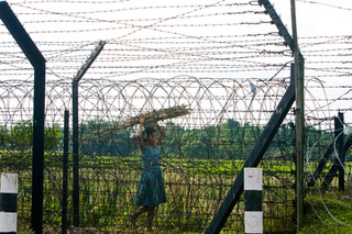 A Bangladeshi immigrant walks near the border near Golakganj at the Indian border patrol checkpost in the late evening before the curfew starts in the border region. Golakganj is located in the Dhubri district of Assam. These immigrants bribe $10 to $12 to cross the border, and once they come to India, they apply for false ration cards to vote. One hundred-and-sixty- mile long India-Bangladesh border passes through Assam where some areas are fenced up, and the rest is open land. Poverty in Bangladesh is so dire that people are trying to cross illegally to India to find work. Most illegal immigrants travel to big cities like Mumbai to work at construction sites or other sectors to earn their leaving
