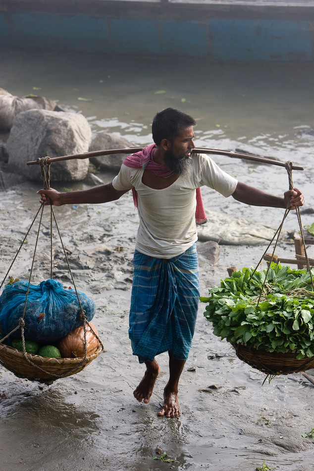 Bangladesh migrants comes in a boat with vegetables to sell in the town of Dhubri, State of Assam in India. Most of these migrants work very hard to earn their money in India