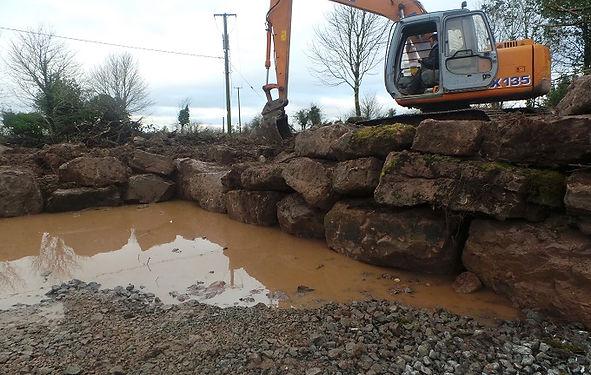 digger building rock wall