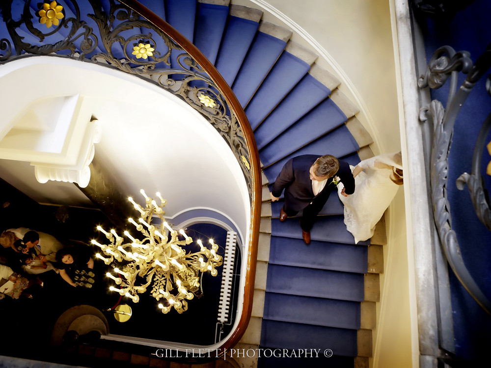The stunning sweeping staircase of Carlton Terrace with teh bride and groom walking down it.