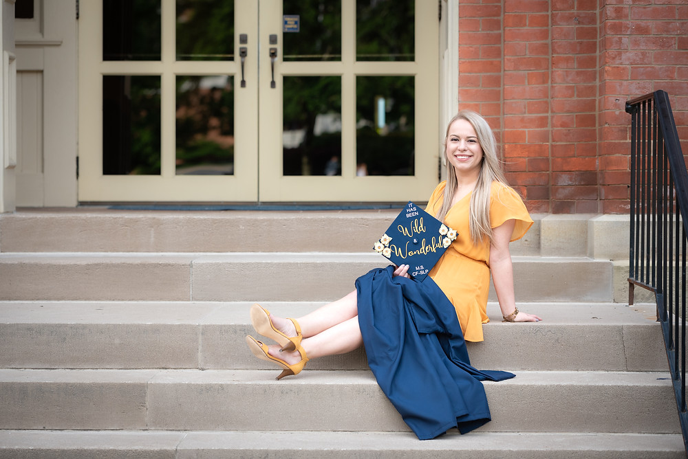 Girl wearing yellow dress holding blue graduation cap and gown at West Virginia University