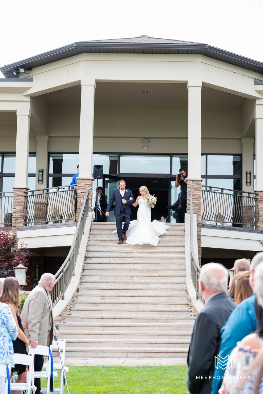 Bride walking down staircase at The Lake Club in Ohio