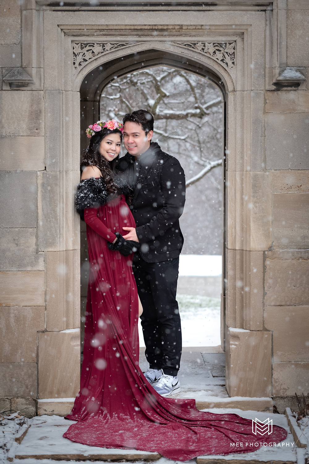 Couple standing in archway at Hartwood Acres during their maternity session