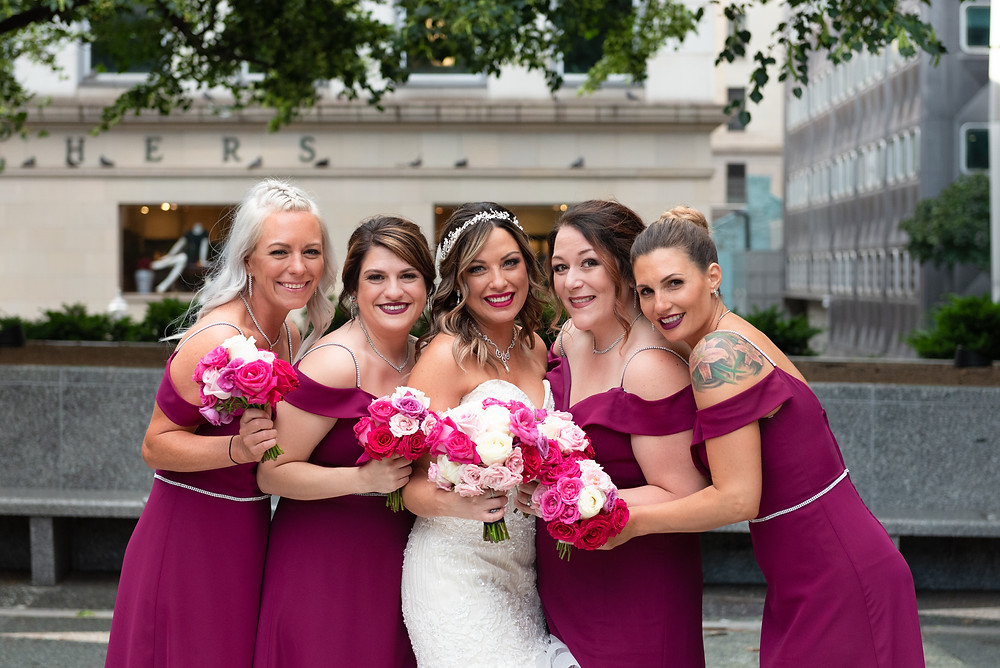 Bride and bridesmaids smiling for a portrait at Mellon Square in Pittsburgh