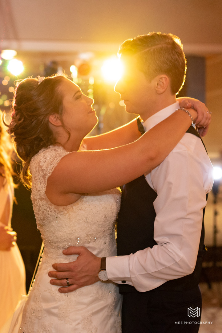 The newlywed's first dance with bright stage lighting shining through them